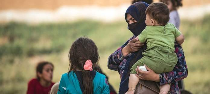 © UNICEF/Delil Souleiman Una mujer y sus hijos llegan a Tal tamer después de ser desplazados por la guerra en el noreste de Siria.