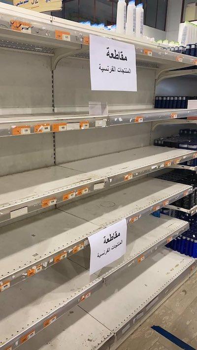 Supermercado en Kuwait con un cartel que dice 'Boicot a los productos franceses' en un estante vacío.