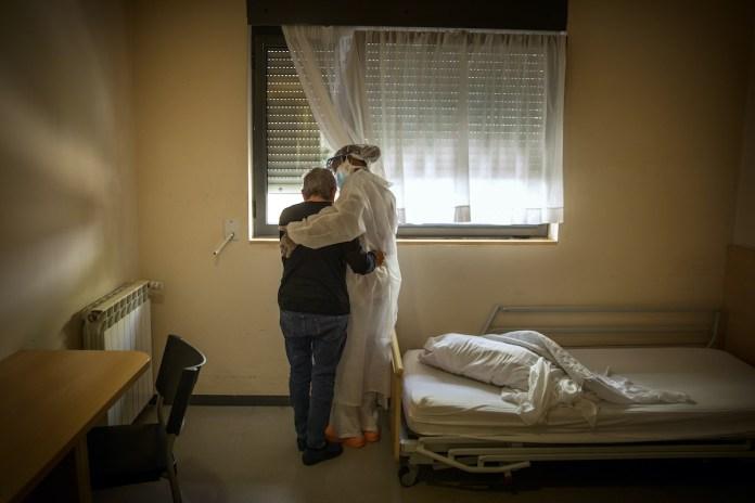 Una anciana se abraza a una trabajadora en la habitación donde permanece confinada