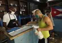 Un cliente paga unos productos racionados que se expenden a través de la libreta de abastecimiento en una bodega del municipio Playa, en La Habana. El aumento de los salarios y pensiones eliminará en Cuba los precios subsidiados de la cuota básica de alimentos y otros productos que el Estado oferta cada mes a los 11,2 millones de cubanos, mediante una cartilla de racionamiento instituida en 1962. © Jorge Luis Baños/IPS