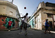 """Un grupo de jóvenes juega con una pelota al atardecer en el barrio de San Isidro, en La Habana. En este barrio se gestó desde 2018 el Movimiento San Isidro que agrupa a jóvenes artistas, periodistas y académicos contestatarios, que en noviembre protagonizaron una huelga de hambre que el gobierno cubano consideró una """"farsa"""". Foto: Jorge Luis Baños / IPS"""