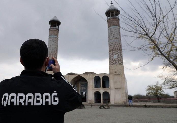 Jugador del Qarabag, desplazado a la localidad de Agdam, recuperada por Azerbaiyán, tras la guerra, haciendo una foto a una mezquita.