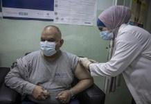 Trabajadores sanitarios administran la primera dosis de la vacuna COVID-19 a personas refugiadas en la Clínica de Vacunación de Irbid, en Jordania. © ACNUR/Jose Cendon