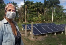 La productora Kety Díaz delante de los paneles solares que instaló en su finca La Cotorra, gracias al Proyecto de Sostenibilidad Alimentaria para Municipios (Prosam), un programa que funciona en Cuba con respaldo de la cooperación internacional. La finca, situada en el municipio de Guanabacoa, en la periferia de La Habana, forma parte de la Cooperativa de Crédito y Servicio José Martí. © Patricia Grogg | IPS