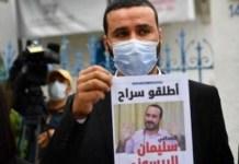 El presidente del Sindicato Nacional de Periodistas Tunecinos (SNJT), Mohamed Yassine Jelassi, muestra una foto de Souleiman Raissouni para mostrar su solidaridad