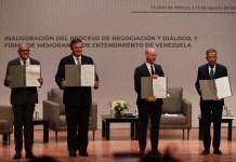 Negociadores del gobierno y la oposición de Venezuela muestran el memorando de entendimiento recién firmado, durante la apertura del diálogo en Ciudad de México. Foto: Gobierno de México