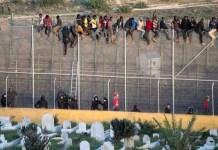 Migrantes encaramados a la valla de Ceuta vigilados por la Guardia Civil.