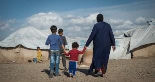 """Noor, de 52 años, camina con sus nietos hacia su carpa en el campamento de Namrud para desplazados internos. Dos de sus hijos trabajaban dentro de un hospital de ISIS, y una de sus hijas estaba casada con un militante de ISIS. """"ISIS no obligó a nadie a ir a trabajar con ellos, pero hizo que la gente tenga hambre, por lo que los forzó indirectamente"""", dice Noor. """"Incluso si nuestros hijos fueran ISIS, ¿por qué deberíamos ser castigados por ello?"""", Pregunta. Foto: Amnistía Internacional"""