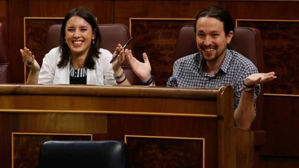 Irene Montero y Pablo Iglesias siguen un debate parlamentario en sus escaños en el Congreso