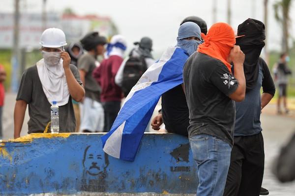 Jóvenes manifestantes nicaragüenses ocultan sus rostros detrás de una barricada en el sur de Managua, levantada con un muro en el que está impresa una imagen del presidente Daniel Ortega. Crédito: Jader Flores/IPS
