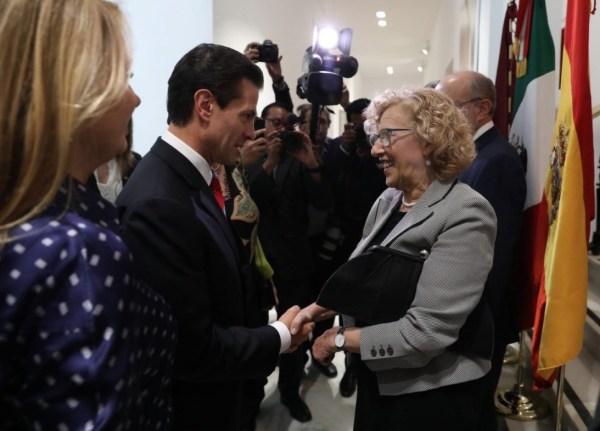 Enrique Peña Nieto y Manuela Carmena se saludan en la entrada de la Casa de México en Madrid