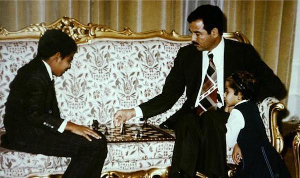 Saddam Hussein juega al ajedrez con uno de sus hijos.