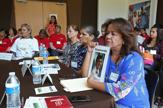 Una mujer sostiene el retrato de un familiar desaparecido durante la intervención de la Comisionada Tracy Robinson (no mostrada en la imagen) después de reunirse con familiares de personas desaparecidas, ejecutadas y/o víctimas de violaciones de derechos humanos, durante la visita de CIDH en la Facultad Libre de Derecho, en Monterrey, Sept. 29, 2015, Mexico. (Ginnette Riquelme para CIDH)