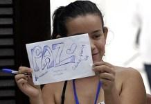 Erika Paola Jaimes, una de las víctimas del conflicto armado de Colombia, sostiene un cartel alusivo a la paz, durante su viaje a La Habana para participar en los diálogos de paz entre el gobierno y la guerrilla de las FARC, que viven su etapa culminante en la capital de Cuba. Crédito: Jorge Luis Baños/IPS