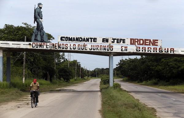 """Imagen de un Fidel Castro joven y combatiente sobre un pequeño puente en una de las carreteras de acceso al puerto de Mariel, junto con una consigna donde se lee: """"Comandante en jefe ordene"""". Frases emblemáticas, imágenes o fotografías del líder de la Revolución Cubana son habituales en los espacios públicos de Cuba, una década después de haber dejado el poder. Crédito: Jorge Luis Baños/IPS"""