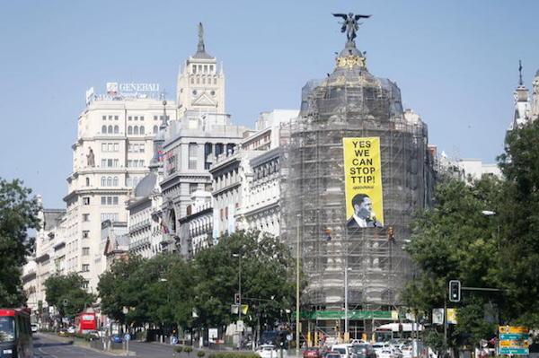 """Greenpeace protesta contra el tratado de libre comercio entre EEUU y Europa durante la visita de Obama a Madrid. En la pancarta, situada en el edificio Metrópoli de Madrid, se puede leer """"Yes we can STOP TTIP"""", con una foto de Obama."""