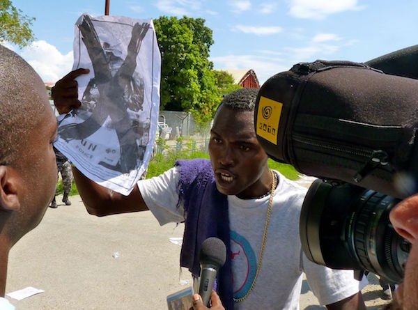 Un manifestante sostiene un cartel contra la ONU durante una protesta frente a una base de la organización en Puerto Príncipe, Haití. Crédito: Ansel Herz / IPS
