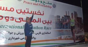 """La corredora Mahsa Torraba delante de una pancarta de la carrera """"I run Iran"""""""