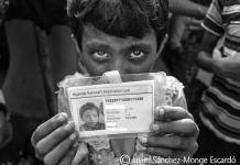 13/NOV2017. Campo de refugiados de Balukhli. Bangladesh: Pequeña rohinyá Una niña Rohinyá muestra la tarjeta de identidad con nacionalidad birmana expedida por las autoridades de Bangladesh (he ocultado sus datos) y que se ven obligados a tener todos los Rohinyás residentes en sus campos de refugiados. Si bien esta tarjeta le da derecho al reconocimiento de su estatuto de refugiada, no le permite salir del campo ni dirigirse hacia ningún otro punto del país, en donde se encuentra transitoriamente hasta que algún día pueda ser reconocida su nacionalidad. Aunque ella nació en el estado Birmano de Rajine, el gobierno Birmano rechaza reconocer su ciudadanía, lo que le otorga la singular condición de ser una apátrida.