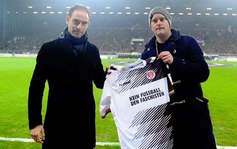 Los dos presidentes, el visitante, Oliver Mintzlaff y el local, Oke Gottlich muestran la camiseta antes de empezar el partido.
