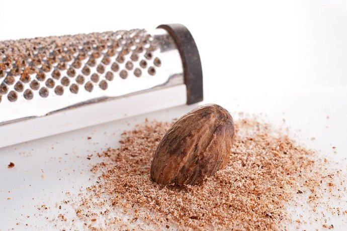 Fresh ground nutmeg with a whole seed grater
