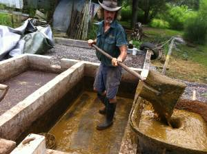 Tom and Zaia shovel cow manure from the biodigester pit