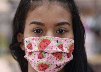 A woman wears a protective mask against the spread of the new Coronavirus (COVID-19) made by seamstresses of the Vila Novo Sao Lucas favela, in Belo Horizonte, Brazil on April 8, 2020. - The Remexe Favelinha atelier which works at the La da Favelinha cultural center of the Vila Novo Sao Lucas favela in the Aglomerado da Serra, will try to produce 6,000 face masks per month for the general population, which follow the protocol and guidelines set by the Brazilian Ministry of Health and cost one US dollar. (Photo by DOUGLAS MAGNO / AFP)