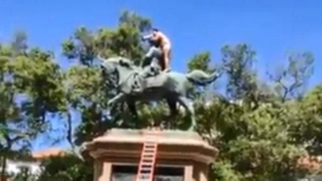 Pitoresco: Nu, homem sobe em estátua dizendo que só descia se fosse vacinado contra COVID-19