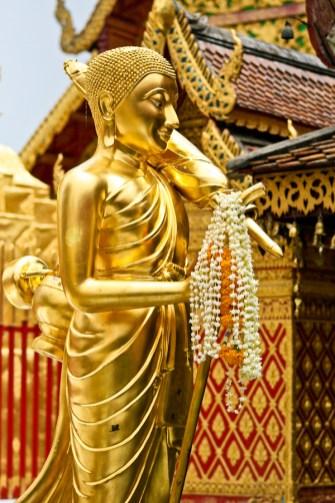 Figurka Buddy w świątyni Wat Phrathat Doi Suthep. Legenda głosi, że świątynia powstała w miejscu, gdzie biały słoń, któremu do grzbietu przywiązano relikwię Buddy zatrzymał się, zatrąbił trzy razy i umarł. (Fot. Kasia Boni)