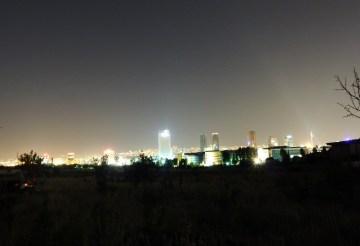 Dwa światy. Na lewo nikłe światełka Obozu, a dookoła zorza z biur, wieżowców i bloków innego świata. (Fot. z archiwum Autostopem ku wolności)