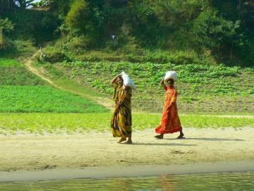Kobiety idace wzdluz rzeki Sanghu.