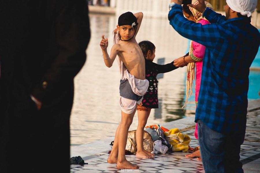 Młodzi sikhowie kąpią się w jeziorze otaczającym Złotą Świątynie