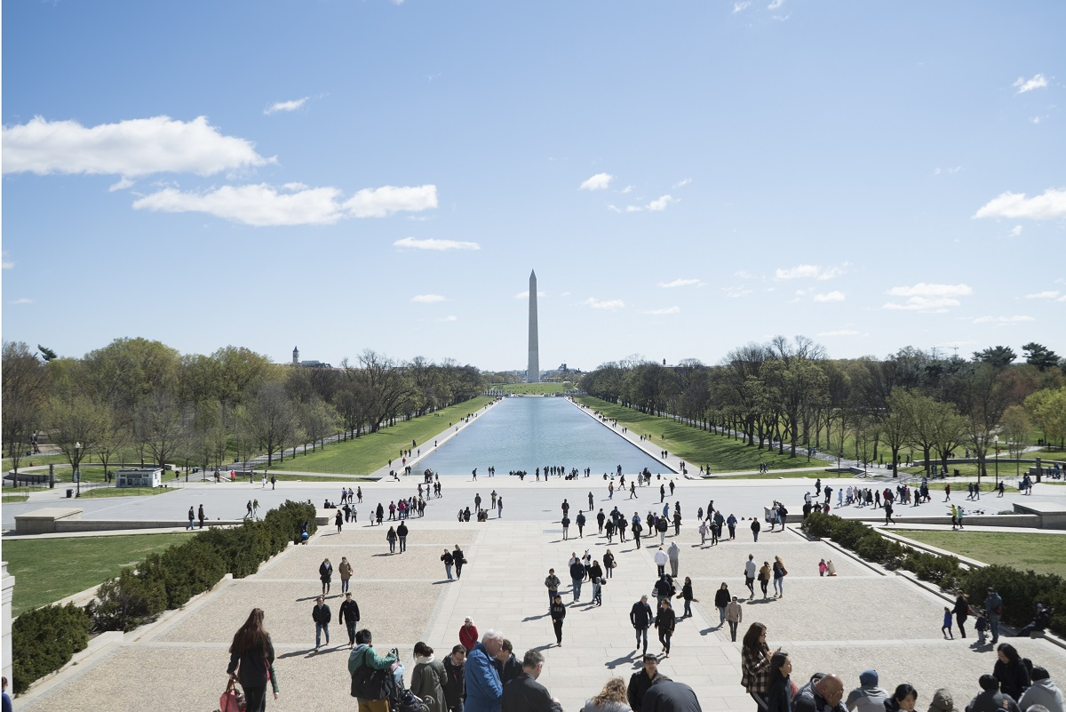 People walking on the steps of the Lincoln Memorial looking towards the Washington Monument.