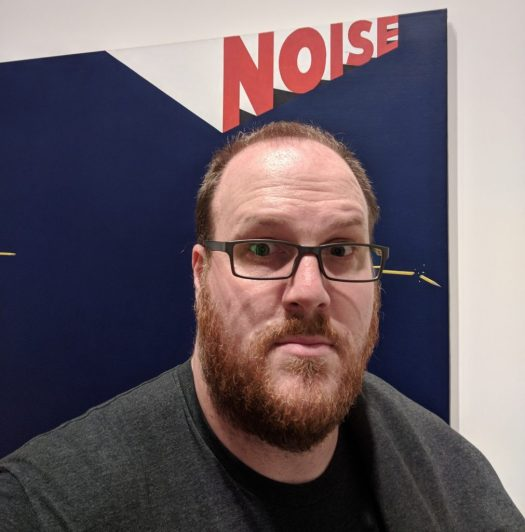 Carl Holscher, the author in front a painting that says NOISE.