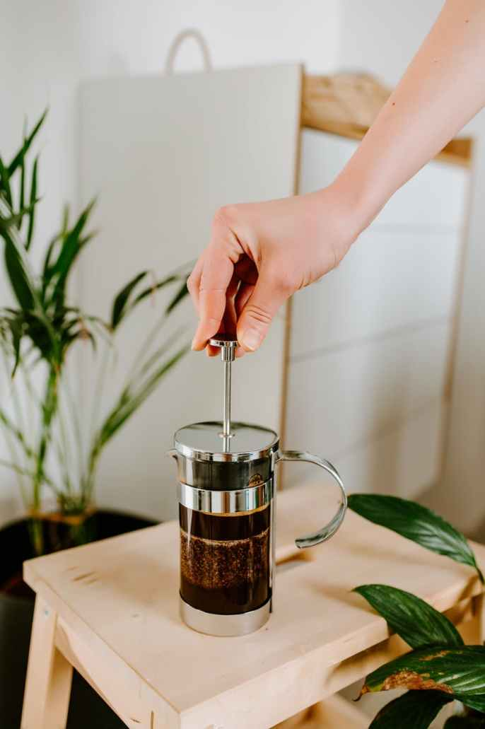 faceless woman using french press while preparing coffee