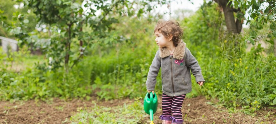 Little kid in the garden with watering can