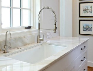 Under-mount, cast iron sink with duel faucets.