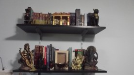 Top shelf has the lararium, and the Bast statues I own. Lower shelf has my dictionaries and related books, my Ganesha and Saraswati statues, and my Earth shrine. Well, what will become the Earth shrine, when I get around to finishing the box.