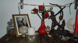 This is the shelf below the ancestor shrine, and we have Hermes and Artemis here. The jar with the coins and the small silver dish in front of His picture belong to Hermes. The white candle is for Artemis, representing the full moon. The serpent and the dish in front of Artemis' statue are Artemis' things. The dish contains the prayer beads I made for Her. Hanging at the back is a cingulum I made some time ago.