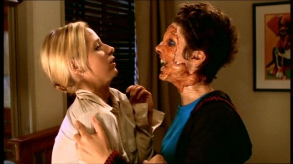 Buffy grapples with Demon Kathy, who's had the skin torn off her face