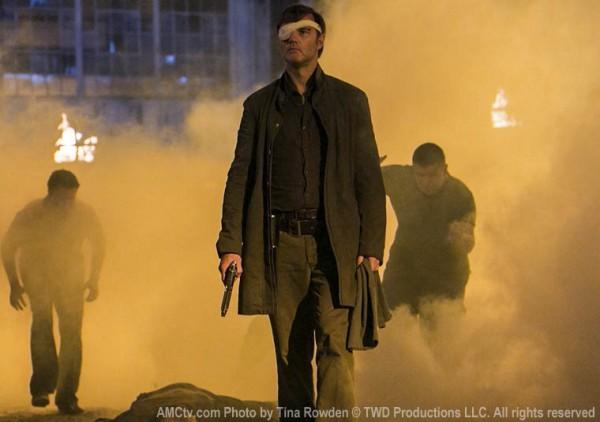 The Governor, with one eye bandaged, walking through smoke