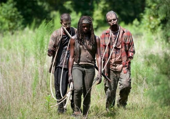 Michonne leading two walkers on a leash