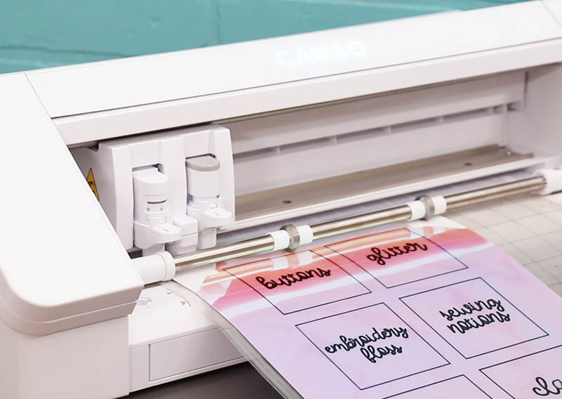 A white Silhouette Cameo 4 machine cuts labels from iridescent sticker paper.