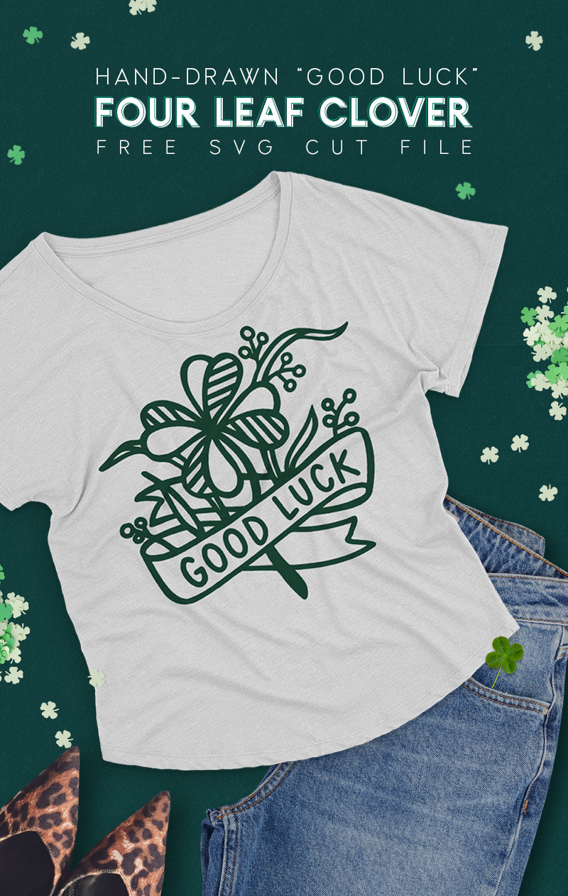 """Gray t-shirt on dark green background surrounded by jeans, leopard print shoes, and paper four leaf clover confetti. The t-shirt has a dark green design on it depicting a hand drawn four leaf clover with a ribbon banner that reads """"good luck."""""""