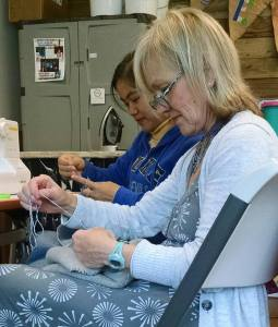 American volunteers sewing with refugee women.