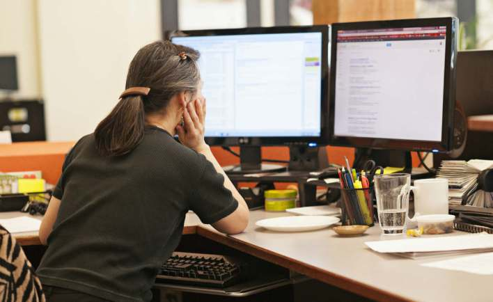 A woman is sitting in front of a computer with two monitors
