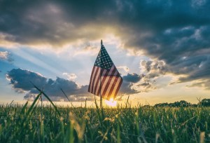 blog picture of american flag in a field during sunset
