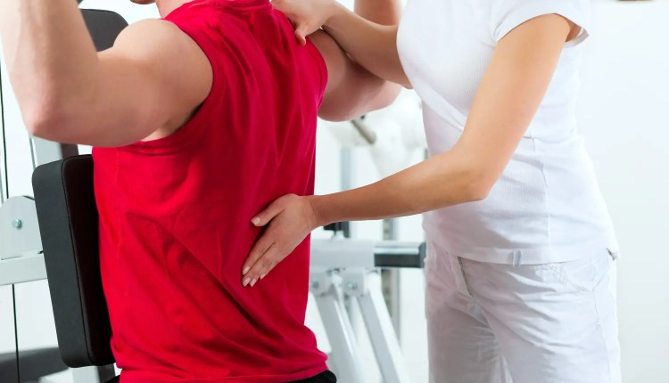 chiropractor works with patient's lower trapezius