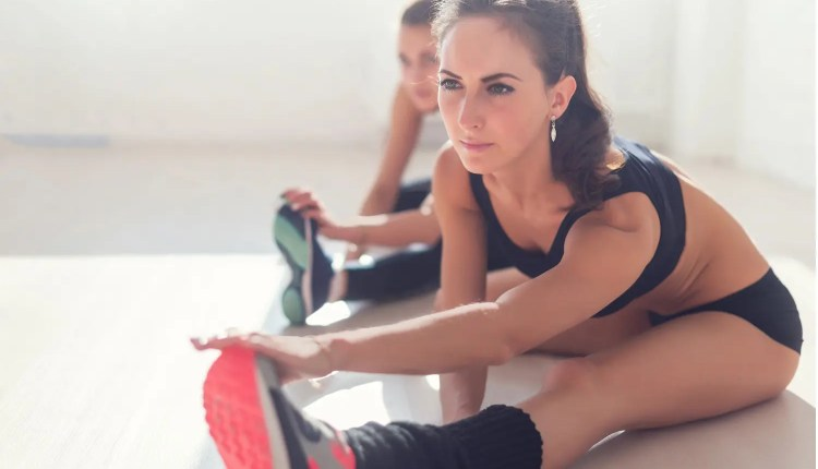 women stretch out legs before workout