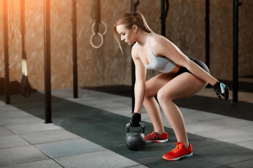 young girl does kettlebell exercises